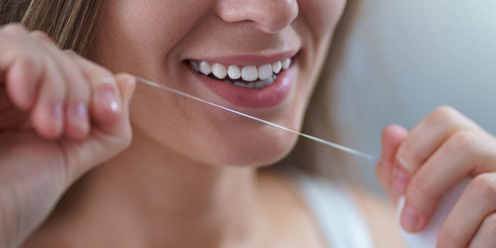 Happy healthy woman uses dental floss for brushing teeth and oral hygiene at home. Teeth oral care